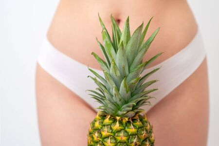 Pineapple on woman's body in white panties background, epilation concept, intimate hygiene. Archivio Fotografico