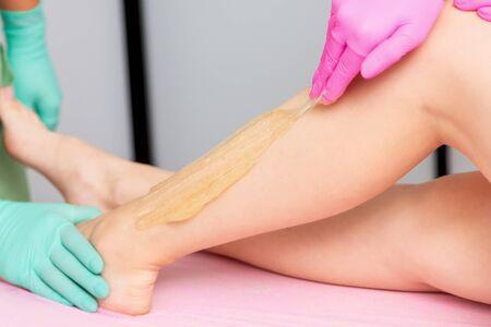 Beauticians hand is applying liquid sugar wax on leg during of sugaring epilation process.