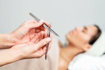 Cosmetologist holds tweezers for eyelash extensions on background of patient, close up.