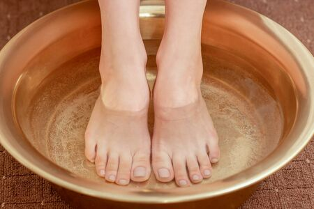 Female feet in bowl with water, close up. Banque d'images