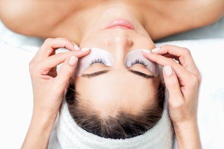 Beautiful woman receiving eyelash extension procedure, close up.