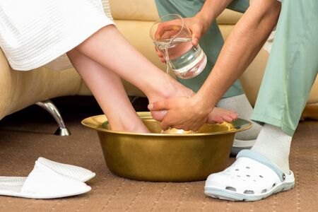Male washes female feet in bowl before massage procedure in spa salon. Banque d'images