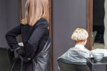 The professional female hairdresser puts on black apron to dye the woman's hair in the hair salon.