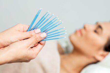 Wimpern Wattestäbchen in den Händen, Einweg-Mikrobürsten zur Wimpernverlängerung auf dem Hintergrund des Patienten, Nahaufnahme.