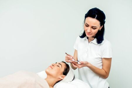 Cosmetologist and patient during eyelash extension procedure on white background with copy space.