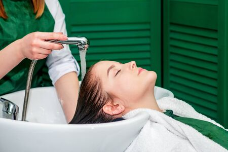 Hairdresser washing woman's hair in sink in beauty salon.