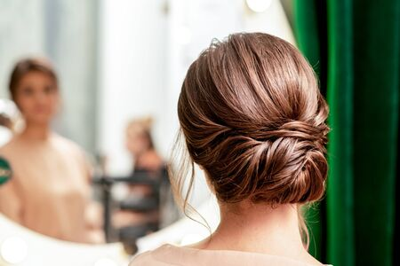Back view hairstyle of pretty brunette young woman in front of the mirror at beauty salon.