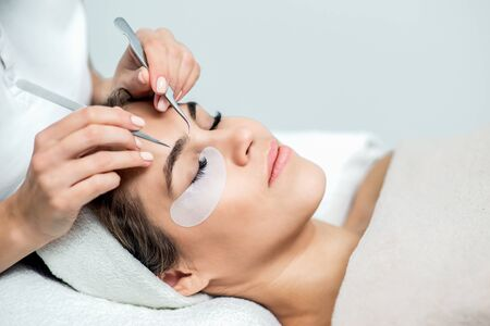 Hands holds tweezers near face of young woman during eyelash extensions process with copy space.