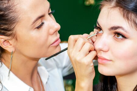 Makeup artist applying eyeliner on eye close up.