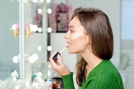 Young woman applies lipstick looking at mirror with copy space.