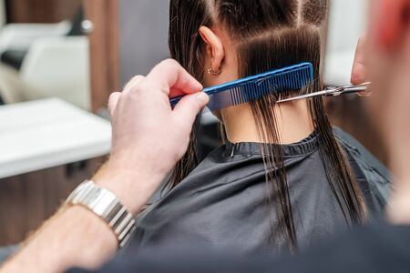 Hairdresser cuts hair of woman in hair salon close up.