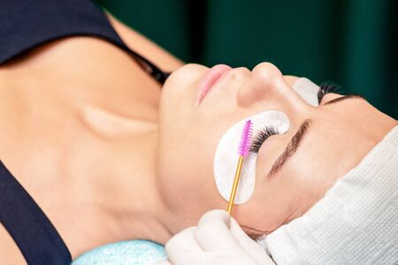 Cosmetologist combs eyelashes with eyelash brush during eyelash extension procedure in beauty salon. Banque d'images