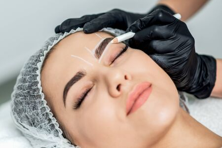 Markup with pencil on eyebrows of yong woman while permanent make up. Фото со стока