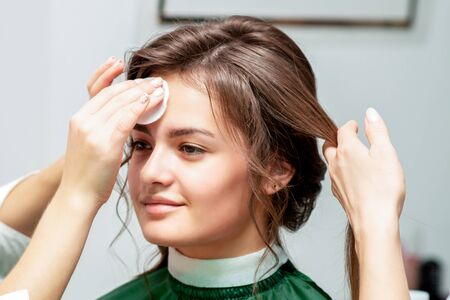 Cleaning face skin of smiling beautiful young woman with cotton pad in beauty salon. Skin care concept.