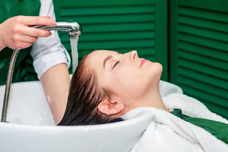 Hairdresser washes hair of woman in sink at beauty salon.