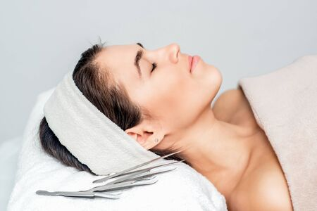 Tweezers near beautiful woman with closed eyes lying ready for skin care and procedures.