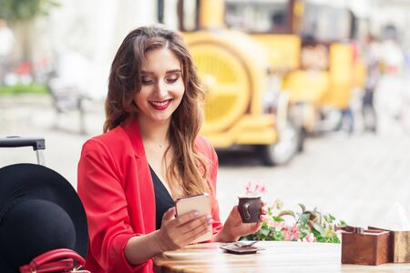 Woman looks in smartphone sitting at cafe outdoors.