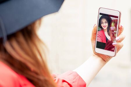 Woman in black hat makes selfie by smartphone.