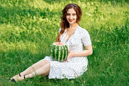 Beautiful young woman with watermelon sits on grass outdoors.