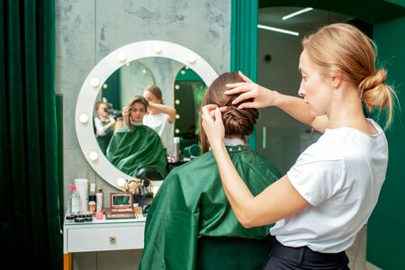 Professional hairdresser makes hairstyle of woman in beauty salon. 写真素材