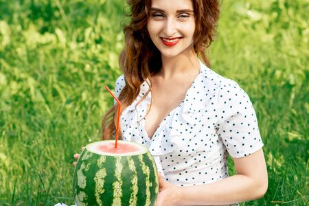 Portrait of beautiful young woman holds watermelon siting on grass outdoors.