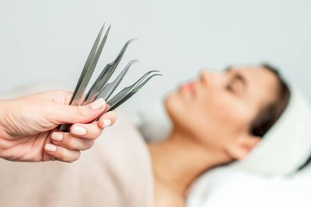 Tweezers in hands of beautician on background of woman before eyelash extensions procedure.