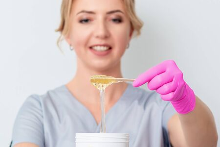 Wax flowing down into container during woman holding in hands on white background. Concept of depilation and epilation.