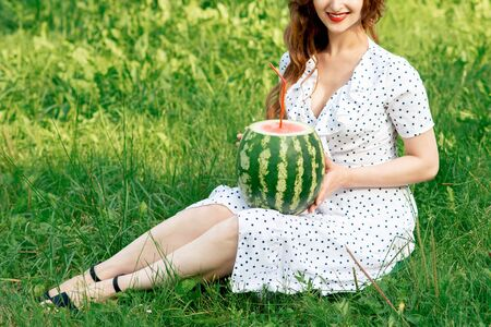 Girl holds whole watermelon with cocktail straw on green grass background.