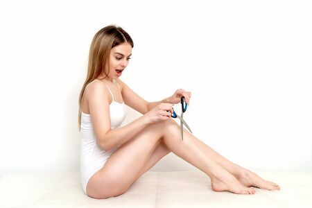 Woman holding scissors near her legs on white background. Depilation and epilation concept.