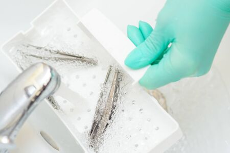 Hand in glove cleans the tweezers with water in tray. Cleaning systems for tweezers.