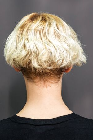 Close up short hairstyle of blonde woman, back view.