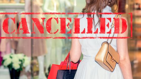 Word CANCELLED on background of two young women in the shopping mall. Coronavirus quarantine. Closed shopping mall. Stock Photo