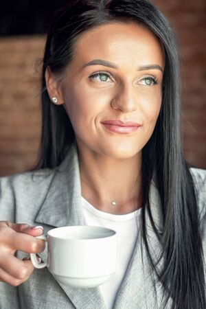 Portrait of business woman is holding white cup of coffee looking away at cafe. Businesswoman in cafe.