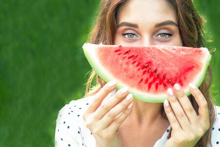Portrait of happy young woman is holding slice of watermelon over green background. Girl with slice of water melon. Фото со стока