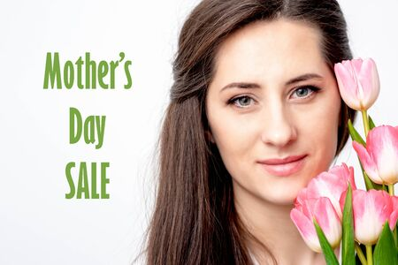 Half face portrait of young woman with pink tulips smiling on white background with text Mother's Day Sale. Banque d'images