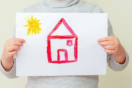 Closeup of child is holding picture of red house with sun at elementary school. Painting concept.