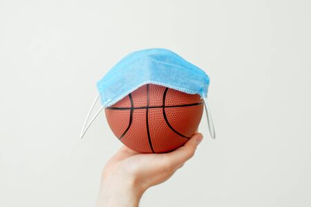 Protective medical mask over basketball ball on male hand due to the coronavirus epidemic on light background. Concept protection from viruses and infections.