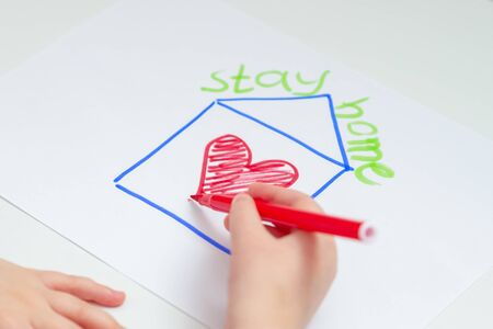 Close up of hand of child drawing house with red heart on the sheet of paper with a painted words Stay Home over the house at home. Stay Home concept. Selective focus.