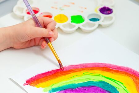 Close up of hand of child with brush drawing rainbow by colorful aquarelle at home. Stay at home concept.