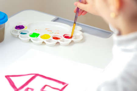 Child is drawing house with watercolors on white sheet of paper. Kid draws house.