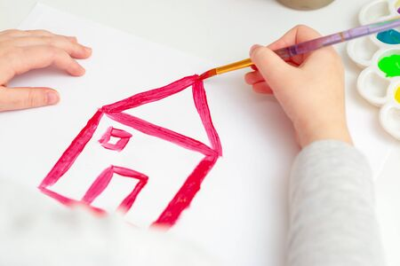 Child is drawing house roof with watercolors on white paper.