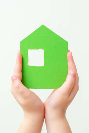 Children's hands holding a green paper house on a white background.