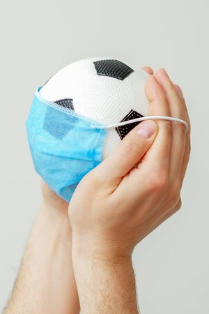 Closeup vertical image of soccer ball with a medical mask in male hands on a gray background. Cancellation of sporting events.