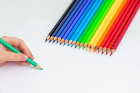 Little girl's hand drawing on blank paper with colorful pencils on white background. Copy space for text. Mockup. Selective focus.