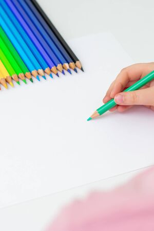 Child's hand drawing by color pencil on blank paper with colorful pencils. Copy space for text. Mockup. Selective focus.