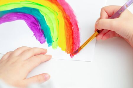 Hands of child drawing colorful rainbow by watercolors on white sheet of paper. Children's creativity concept.