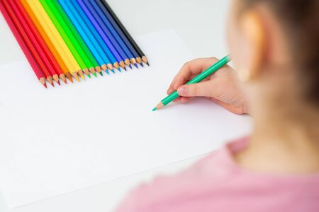 Cute little child is drawing by colored pencils on white paper. Copy space for text. Mockup. Selective focus. Zdjęcie Seryjne