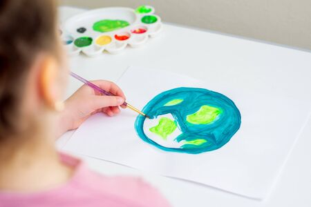 Little girl is drawing earth by watercolors on white paper. Earth Day concept.