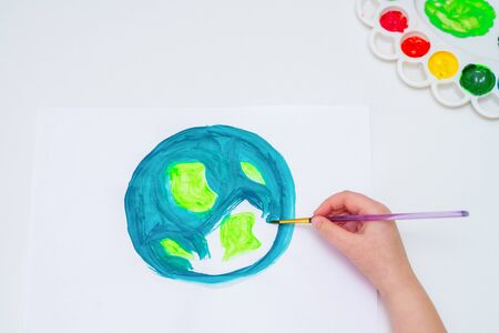 Top view of little girl is drawing earth by watercolors on white paper. Earth Day concept.