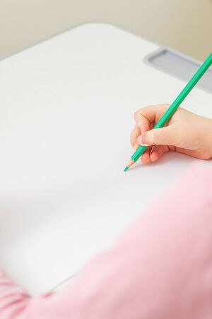 Vertical image of girl's right hand holding pencil over a white blank sheet of paper on a white desk. Copy space for text. Mockup. Selective focus.